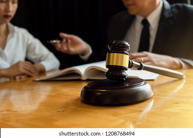 Judge gavel with Justice lawyers having team meeting at law firm background. Concepts of Law and Legal services.
