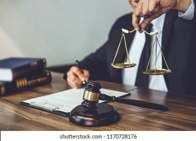 Judge gavel with Justice lawyers, Lawyer or counselor working on a documents and holding balance in Courtroom, Justice and Law concept.