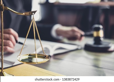 Judge gavel with Justice lawyers, Gavel on wooden table and Counselor or Male lawyer working on a documents. Legal law, advice and justice concept.