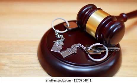 Judge gavel and key chain in shape of two splitted part of house on wooden background. Concept of real estate auction or dividing house when divorce, division of property, real estate, law system.