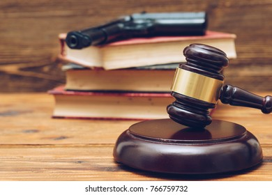Judge gavel, law books and gun  on a wooden background