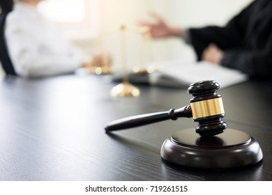 Judge gavel with lawyers advice legal at law firm in background. Concepts of law, services.