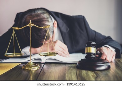 Judge gavel with lawyers, Gavel on wooden table and Counselor or Male lawyer is tired and migraine headaches during hard working on a documents at law firm. Legal law, advice and justice concept.