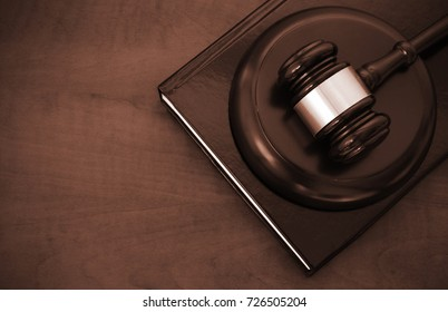 Judge gavel and legal book on brown wooden table