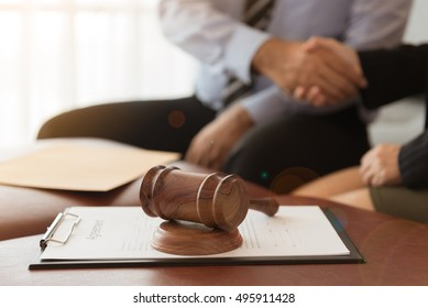 Judge gavel with legal documents and attorney hold hands client and give legal advice.