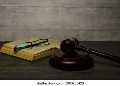 judge gavel lie beside a book on dark background