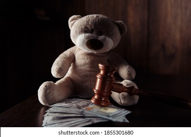 Judge gavel, money banknotes and teddy bear. Divorce and alimony concept