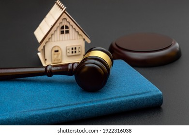 Judge gavel with notepad and model of house on black background.