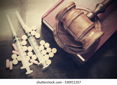 Judge gavel on red legal book with drugs and syringes