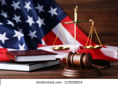 Judge gavel with scales, books and american flag on wooden table
