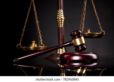 Judge gavel and scales of justice over balck background
