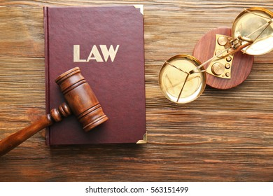 Judge gavel with scales and Law book on wooden background