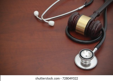 Judge gavel and stethoscope on wooden background with room for text, malpractice concept