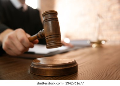 Judge with gavel at table in courtroom, closeup. Law and justice concept