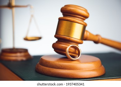 Judge gavel with wedding ring on law book