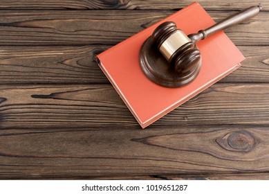 a judge hammer, a book on a wooden background. jurisprudence.