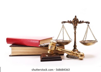 Judge Hammer, bronze scales, a book about the laws and pen on a white background