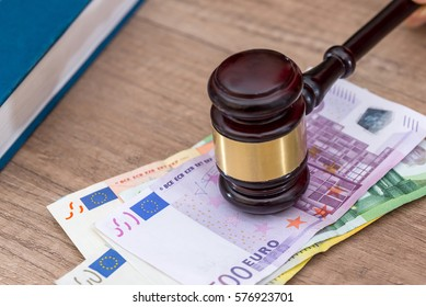 Judge hammer and different euro banknotes on desk.