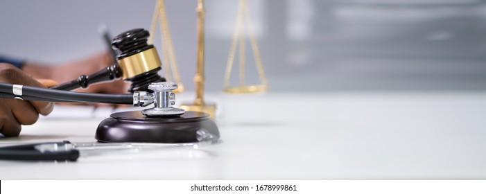 Judge Hands Striking Gavel Near Stethoscope In Courtroom