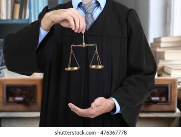 Judge holding scales of justice on blurred books background.