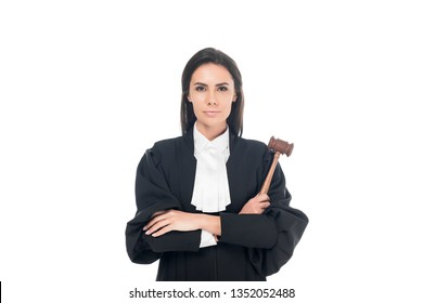 Judge in judicial robe holding gavel and standing with folded arms isolated on white