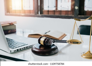 Judge office  with laptop computer,pen,legal books,scale and gavel on white desk.justice and law concept.