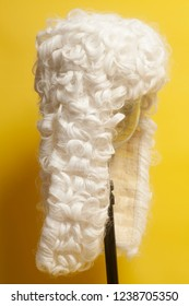 Judge wig on yellow background.