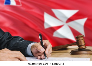Judge writing on paper in courtroom with Wallis And Futuna flag background. Wooden gavel of equality theme and legal concept.