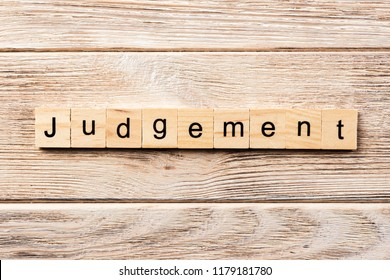 judgement word written on wood block. judgement text on table, concept.