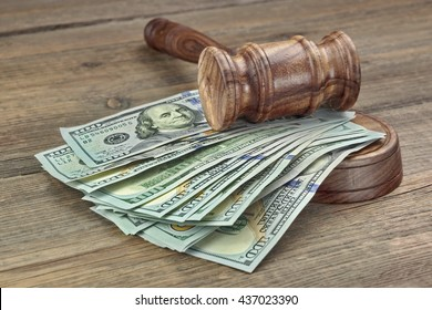 Judges or Auctioneers Gavel Or Hammer And Big Money Stack On Wooden Bench Or Wooden Table Background, Concept For Financial Crime, Close Up