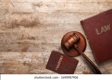 Judge's gavel, book and passport on wooden background