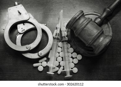 Judge's gavel with handcuffs, drugs and syringes on wooden table, drugs concept