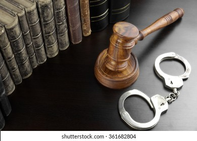 Judges Gavel, Handcuffs And Old Law Book  On The Black Wooden Table Background In The Back Light. Overhead View. Lawsuit or Bail Or Arrest Concept