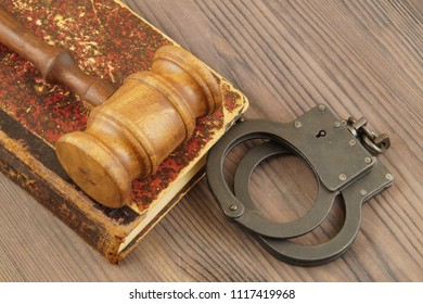 Judge's gavel with handcuffs and old legal book on wooden table