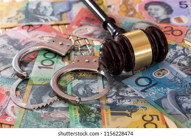 Judge's gavel with handcuffs on australian dollars