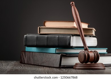 Judge's gavel and heap of books on dark background. Legal knowledge and juridical system concept.
