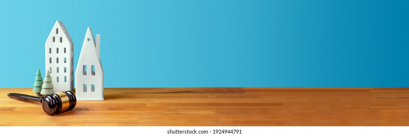 Judges gavel, houses and trees on table in front of a blue background. Law firm