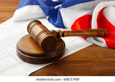 Judge's gavel with individual tax return form and American flag on wooden table