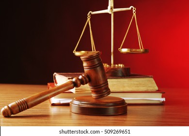 Judges gavel with justice scales and books on wooden table and red background