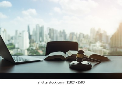 judges gavel, law books and computer on desk in lawyer office and city view. legislator and legal advice concept.