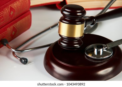 Judges gavel  with law books and medical stethoscope on white table in a courtroom or enforcement office, close-up. selective focus. Medicine law concept