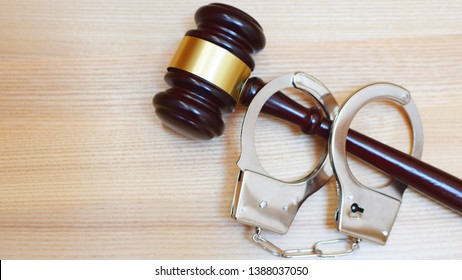 Judges gavel or law mallet and handcuffs on wooden background. Judgement, legal system, time for justice, bribery and corruption problems concept.