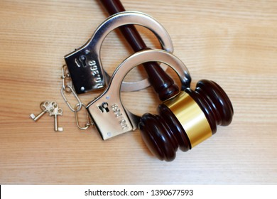 Judges gavel or law mallet, handcuffs and key on light wooden background with copy space. Judgement, legal system, time for justice concept.