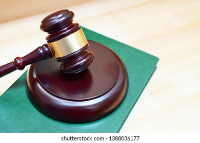 Judges gavel or mallet on green law book on wooden table. Legal law, justice system, education and judgement concept.
