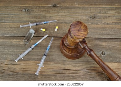 Judges Gavel And Medical Drugs On Grunge Wood Table