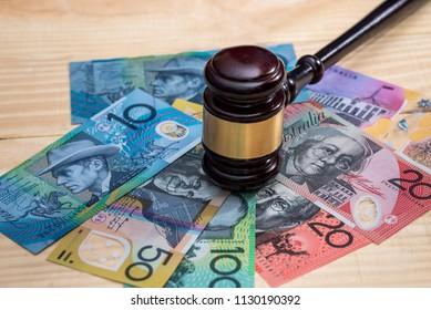 Judge's gavel on australian dollar banknotes closeup