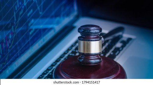 Judges gavel on keyboard with glowing computer screen monitor background.