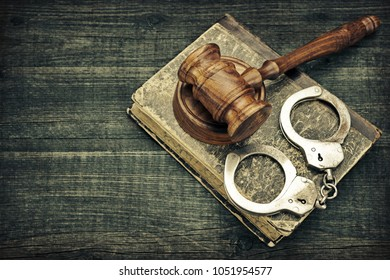 Judges Gavel On Sound Block, Old Law Book  And Handcuffs On The Rough Wooden Textured Table Background. Top View. Justice Concept