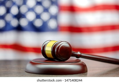 judge's gavel on table with usa flag on backdrop
