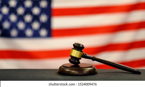Judge's gavel and over USA flag. Symbol for jurisdiction. Law concept a wooden judges gavel on table in a courtroom or law enforcement office on blue background. Copy space for text